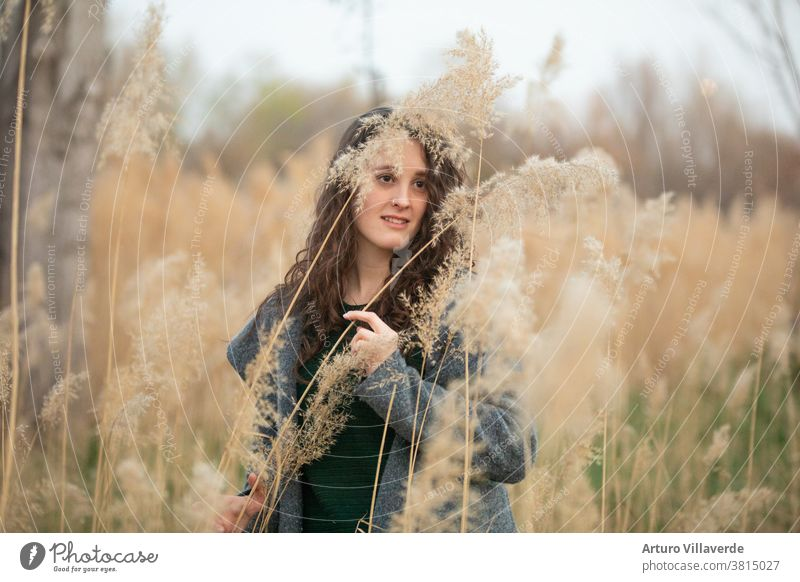 portrait of a woman surrounded by reeds. He is wearing a gray jacket. abstract adult asian background backlight beautiful beauty brunette chinese cute elegance