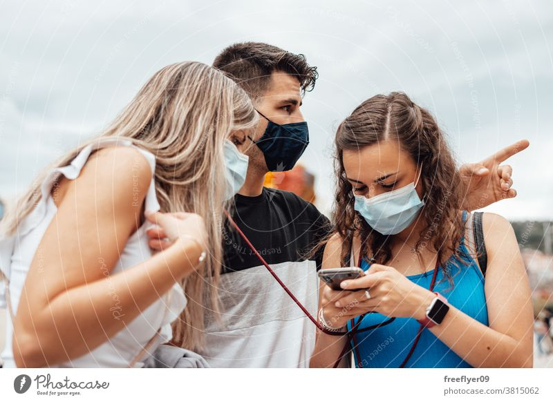 Group of friends with surgical masks searching on a smartphone orientation group caucasian cassual attire bilbao young tourism travel tourists pandemic