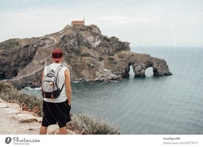 Young man with a hat in front of the Gaztelugatxe Island one tourist backpacker tourism visiting sightseeing romantic island vizcaya spain bermeo X century