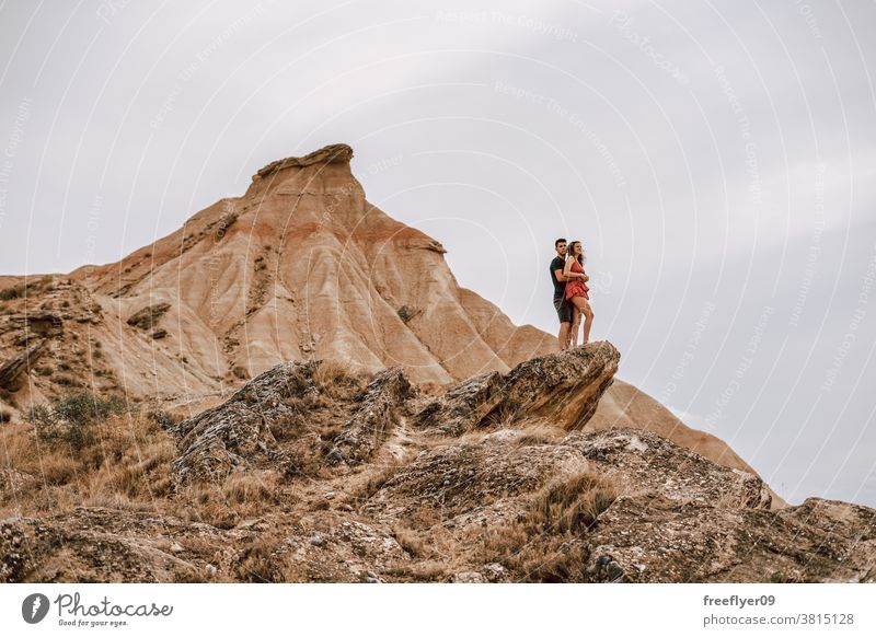 Couple on top of a rock on a desertic landscape couple honeymoon adventure romantic heterosexual freedom sightseeing walking tourists sports clothing young 20s