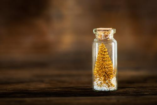 Miniature Gold Christmas Trees in Glass Baubles tree christmas xmas baubles glass bottle mini miniature unusual postcard background holiday year new pine