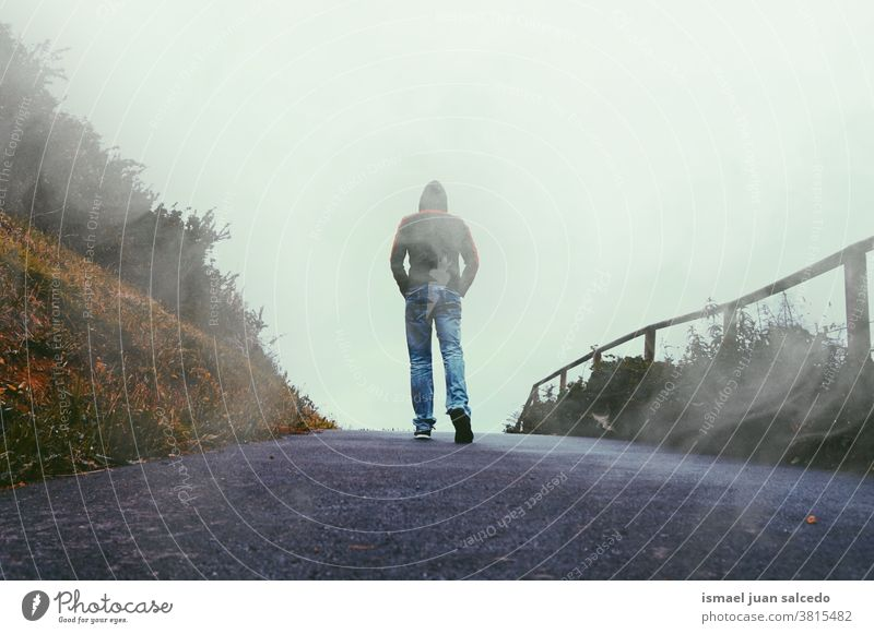 man walking in the mountain, foggy day person people alone loneliness nature landscape road forest view traveling standing adventure lifestyle countryside field