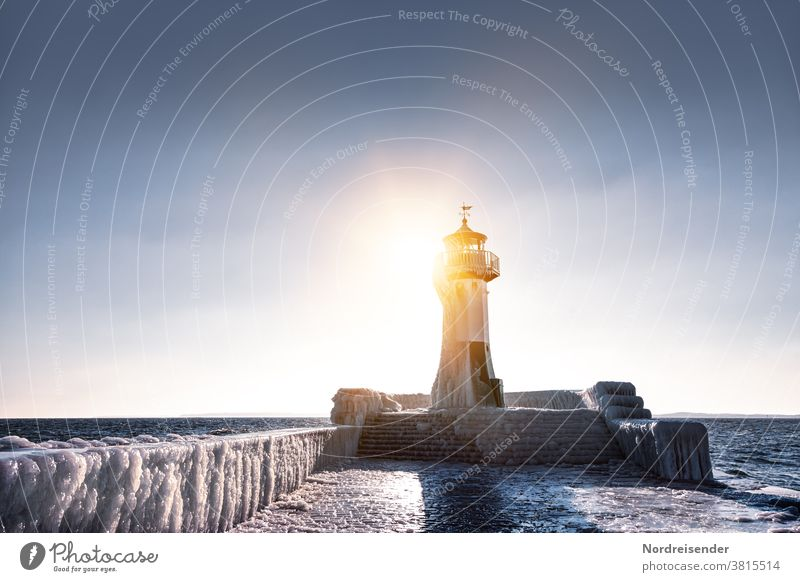 Iced pier with lighthouse of Saßnitz in winter Back-light Sunbeam Sunlight Light Reflection Light (Natural Phenomenon) Copy Space top Copy Space right