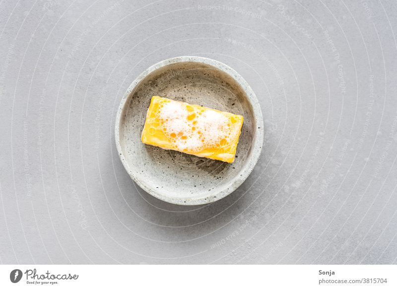 A yellow bar of soap with foam on a grey plate. Soap Yellow Foam grey background Wash hands Clean hygiene Healthy care Water Protection covid-19 coronavirus med