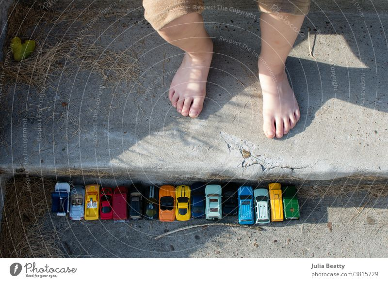 Toy cars in a row on concrete stairs near child's feet; outdoor play toy car toy cars Playing Playful Toes Concrete Line lined up Row free play candid childhood