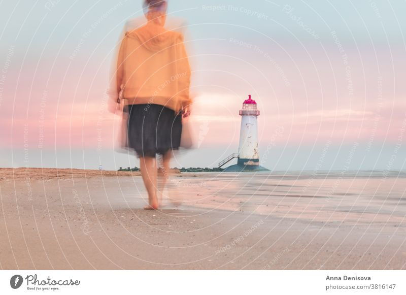 Blurry motion of moving woman towards Lighthouse blurry point of ayr talacre lighthouse shore wales sea walking person travel lady beach coast landscape britain