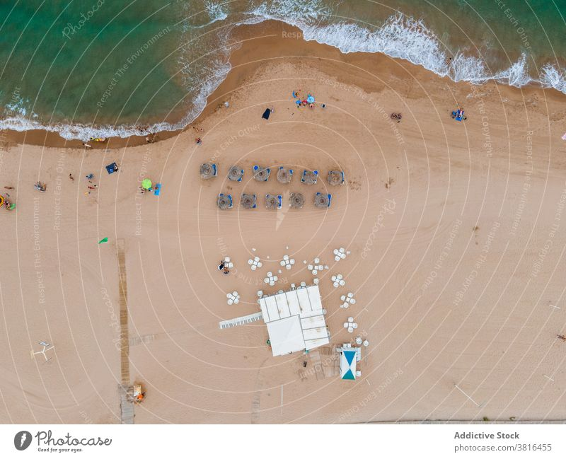 Sandy beach near waving sea turquoise sand scenic seascape deckchair lounger umbrella resort coastline summer ocean nature vacation holiday idyllic wave