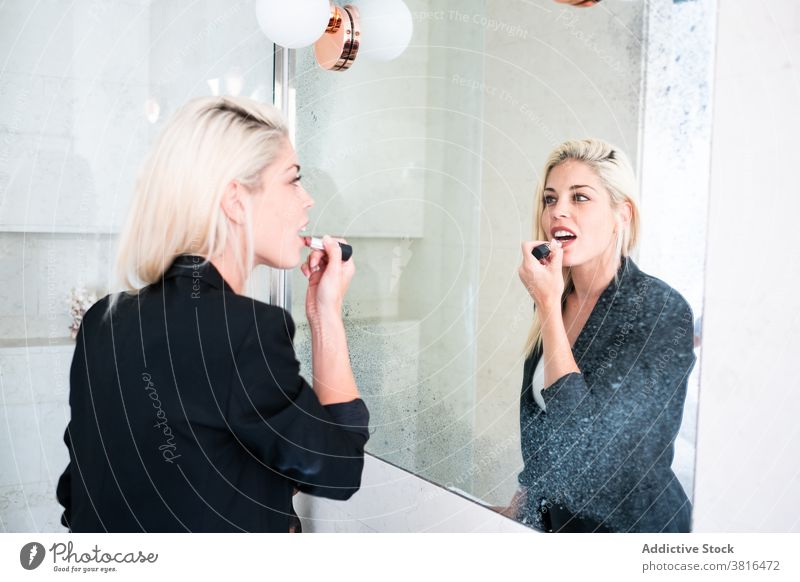 Blonde woman applying lipstick near mirror makeup morning routine reflection cosmetic beauty young female paint bathroom skin care daily treat lifestyle lady