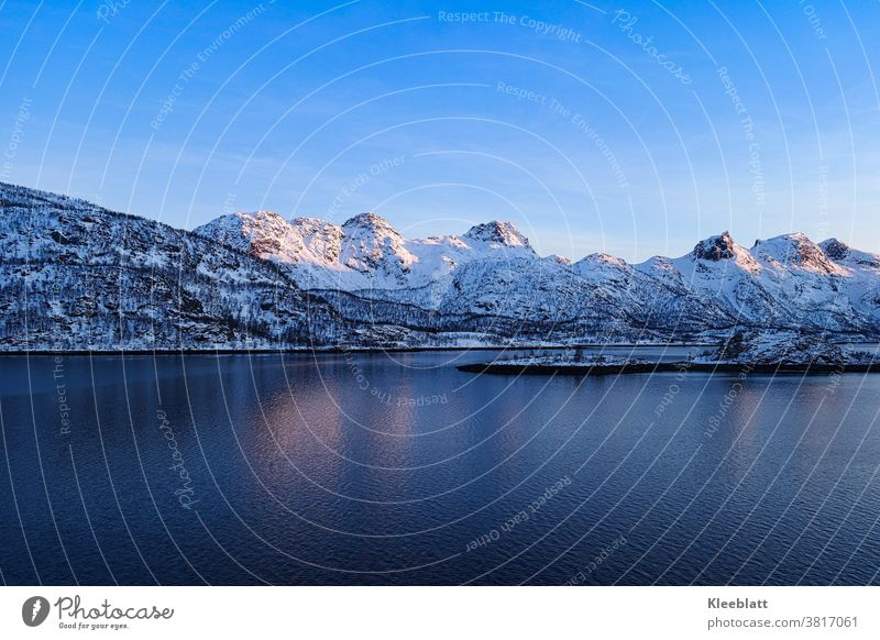 Norway - Trollfjord , Lofoten mountains rise into the blue almost cloudless sky at the beginning of sunset Lofotes Vacation & Travel Ocean Maritime experience