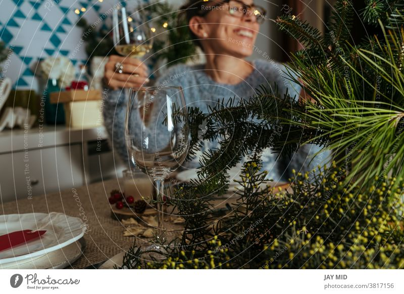 family chatting at christmas dinner, two sisters sitting at the decorated table with glasses of white wine in hand. thanksgiving women smile together talk