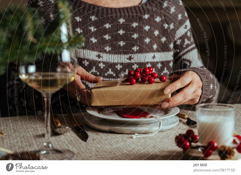 Woman opening christmas gift while sitting at table setting, Family Together Concept woman christmas table setting happy people present love holiday together