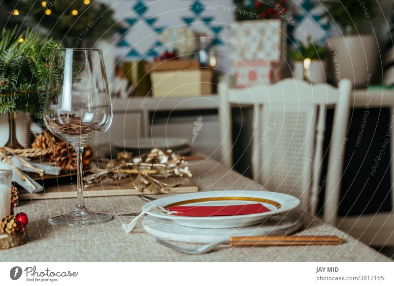 Homely christmas table setting, with pine branches rustic tablecloth in the living room of home. European style with Christmas lights. thanksgiving
