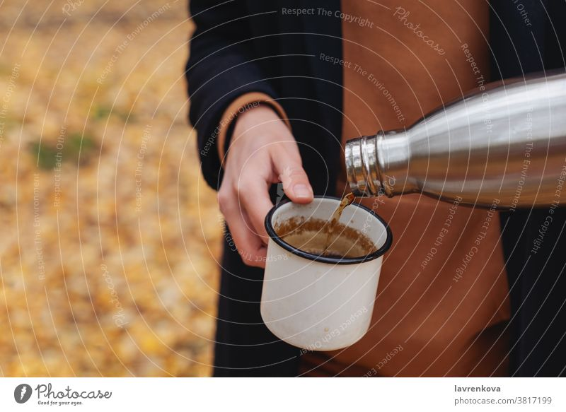 Closeup of female hands pouring hot tea into enamel cup outdoors mug hiking drinking smiling leisure thermos picnic travel activity camping autumn faceless