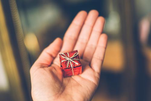 Hand holds a small red gift for birthday or Christmas. Gift Birthday Red Small Packaged Surprise Bow Christmas gift Give Donate