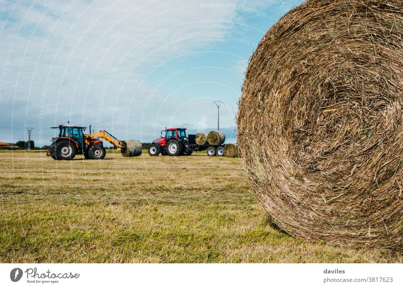 Rounded straw bale and two tractors working in the background harvesting campaign package grassland scenery vehicle machine compactor pile agricultural autumn