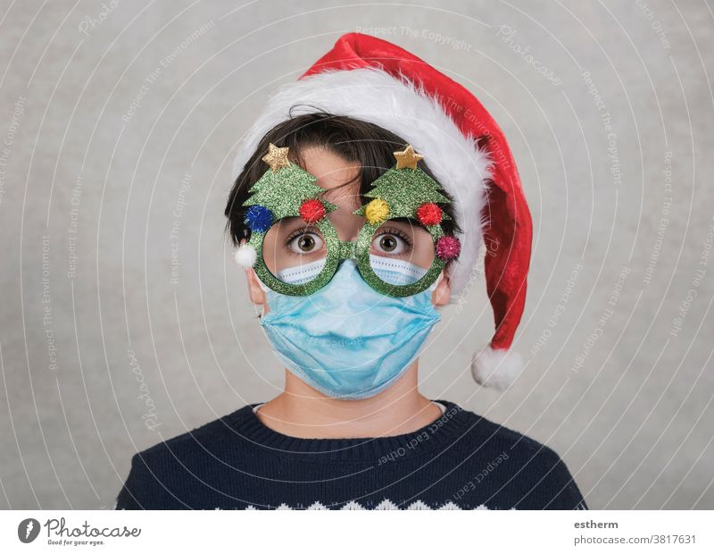 Merry Christmas, Funny child with medical mask and funny christmas glasses santa claus coronavirus Christmas Eve 2019-ncov epidemic covid-19 pandemic quarantine