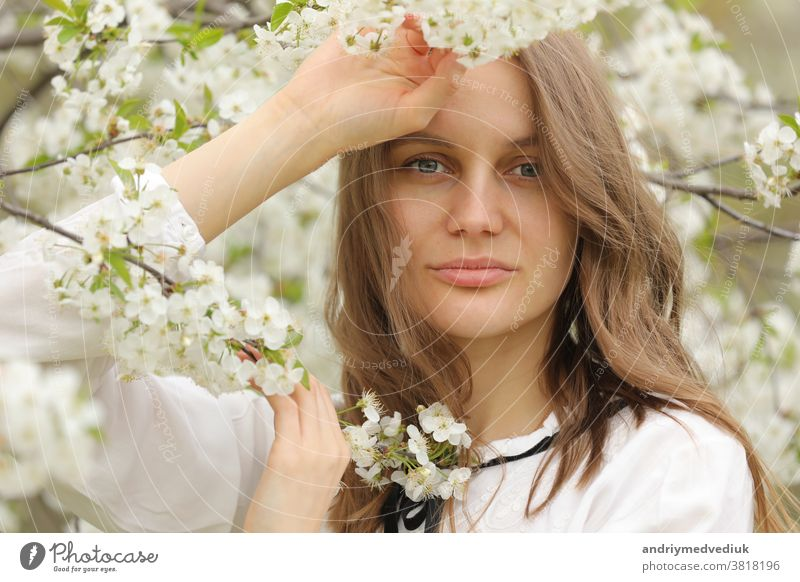 portrait of a happy girl in spring flowers. A beautiful young girl with flowers bouquet near a floral wall. hair summer healthy cute dress nature woman romance