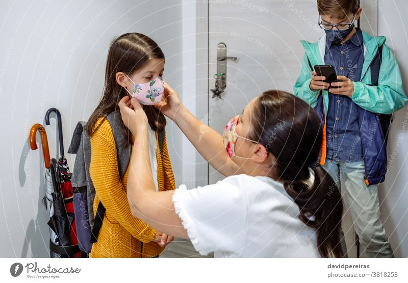Mother putting the mask on her daughter mother preparing face mask go to school covid-19 coronavirus protective mask correctly fitting mask reusable cloth mask