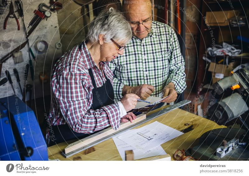 Senior couple in a carpentry carpenter senior looking plans working together workshop wood mature designing business carpentry shop caucasian home retirement
