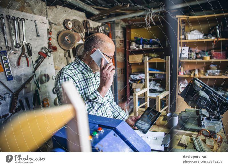 Carpenter in his workshop carpenter mobile cell phone talking tablet design custom made miter carpentry man senior business work bench waist up mature male