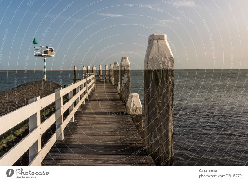 A pier juts out into the sea, a starboard buoy to the left, striking horizon. Footbridge boards Wood Navigation mark ton Starboard buoy Ocean Horitont Water