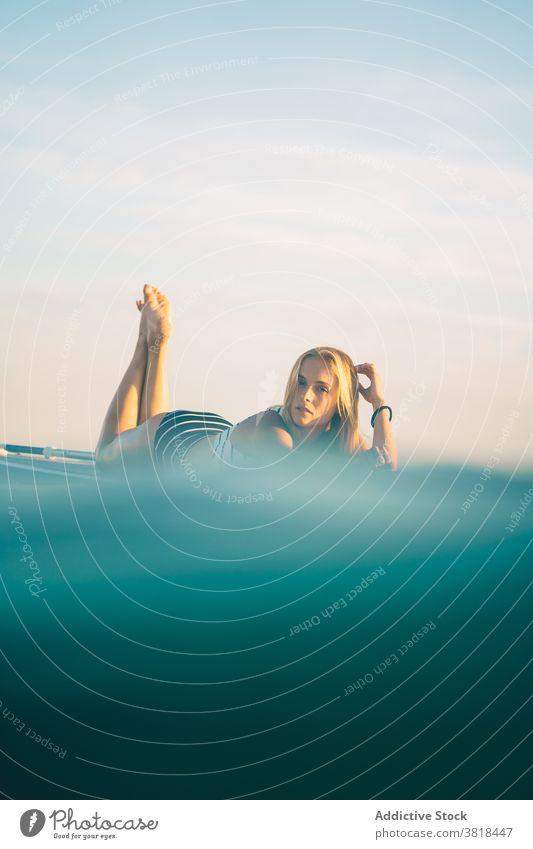 Serene woman on surfboard in sea lying relax sunset slim swimsuit water wave female sky recreation ocean summer swimwear rest weekend peaceful holiday calm