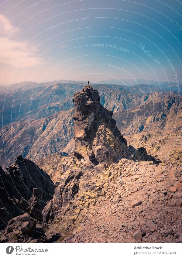 Unrecognizable tourist on rough rock under cloudy sky traveler admire ridge highland nature wanderlust explore blue sky breathtaking mountain journey