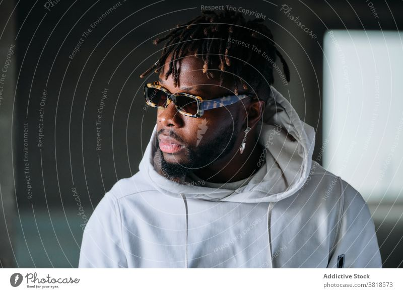 Black man in underground in city style male ethnic black african american dreadlocks hairstyle ring serious informal appearance sunglasses unemotional jewelry