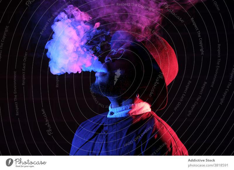 Ethnic man smoking in studio with neon lights smoke vape steam style illuminate dark male ethnic black african american sunglasses hat trendy hipster cool