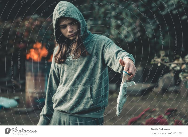 boy with long hair in green hoodie holding a glove with stuck ice plates garden gardening frozen cold Water Frost hand human human hand fingers garden glove