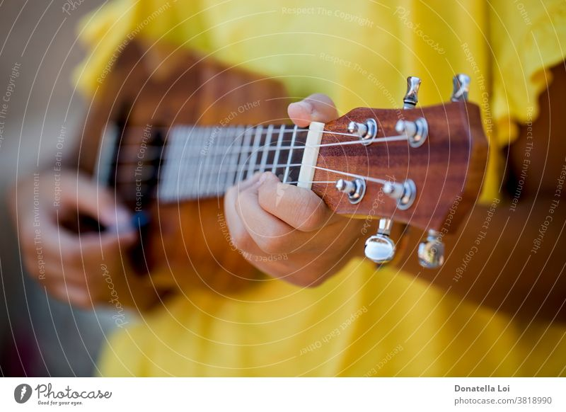 Close up of girl with ukulele artist differential focus fingers hands instrument lifestyle melody music musical musician one outdoors person play playing sing