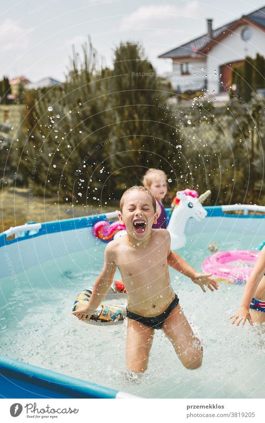 Boy jumping and splashing in a pool authentic backyard childhood children family fun garden happiness happy joy kid laughing lifestyle playful playing real