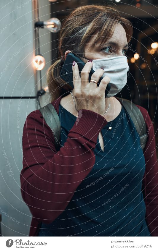 Young woman talking on phone standing in a front of restaurant downtown wearing the face mask to avoid virus infection call care caucasian chat contagious