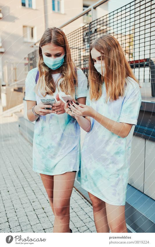 Young women using smartphone wearing the face masks to avoid virus infection standing in a street caucasian cellphone conversation covid-19 female lifestyle
