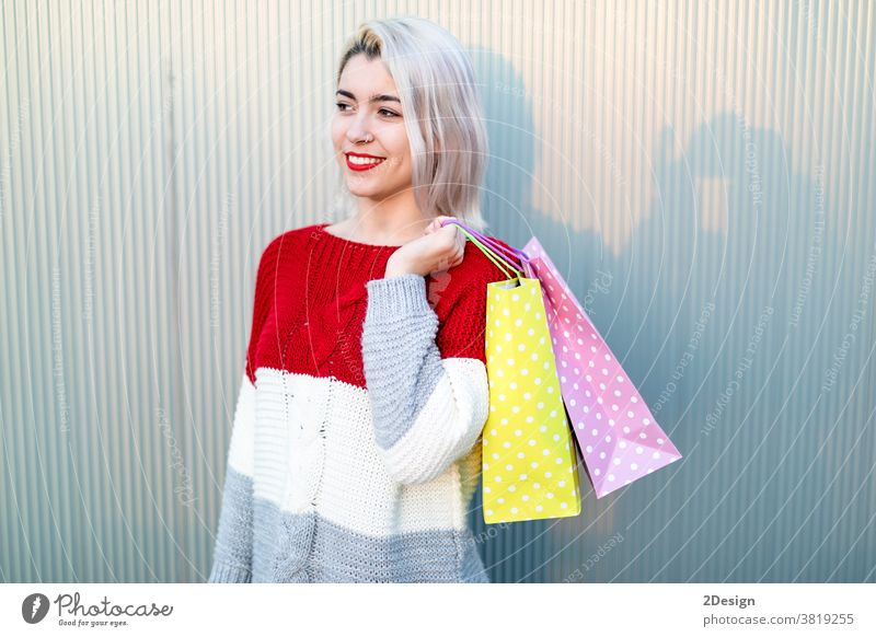Portrait of young happy smiling woman with shopping bags standing 1 shopper happiness beautiful female purchase girl shopaholic person outdoor lady pretty