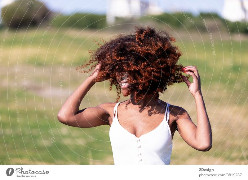 Beautiful afro american woman with white dress sitting on grass in a park in sunny day. 1 african american female young portrait outdoor person lady lifestyle