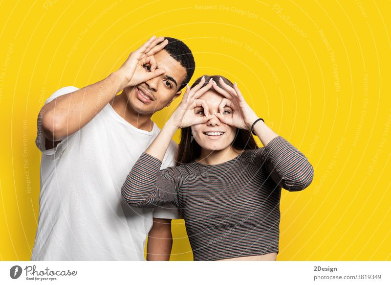 Portrait of funky cheerful couple making binoculars with fingers wearing casual shirts isolated on bright yellow background relax 2 comic playful laughter