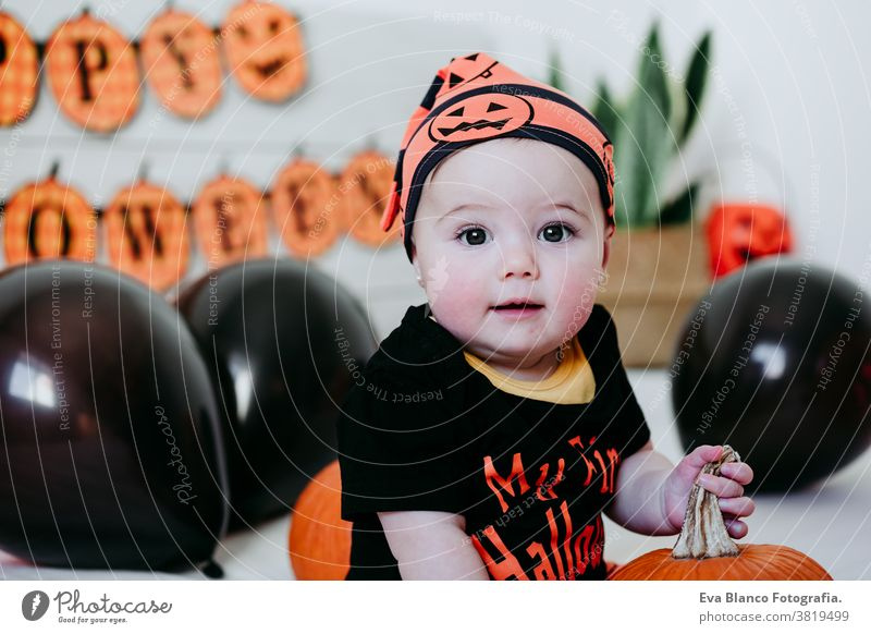 cute baby girl in halloween costume at home, sitting on bed with Halloween decoration, Lifestyle indoors trick or treat pumpkin balloons orange october house