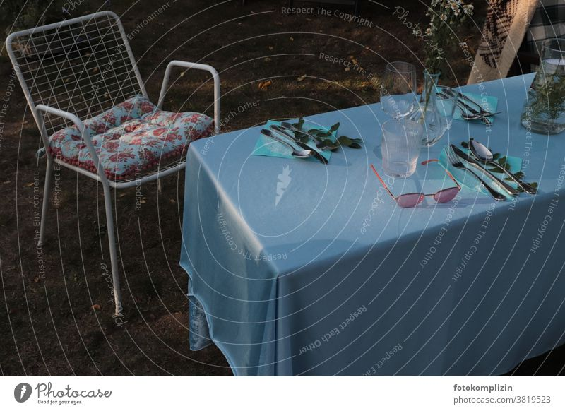 set garden table with blue tablecloth, garden chair, flower cushion and sunglasses Garden Life Outdoor furniture Summerfest laid table in common tepid