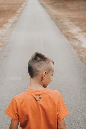 child from behind with orange t- shirt on a road innocence t-shirt orange color style inspirational men boys Males one person Rear view childhood lifestyles
