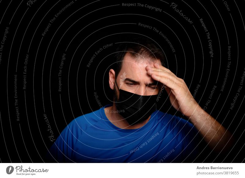 Bearded man dressed in blue t-shirt and with a black mask to protect himself from coronavirus posing against black background white doctor medicals one person