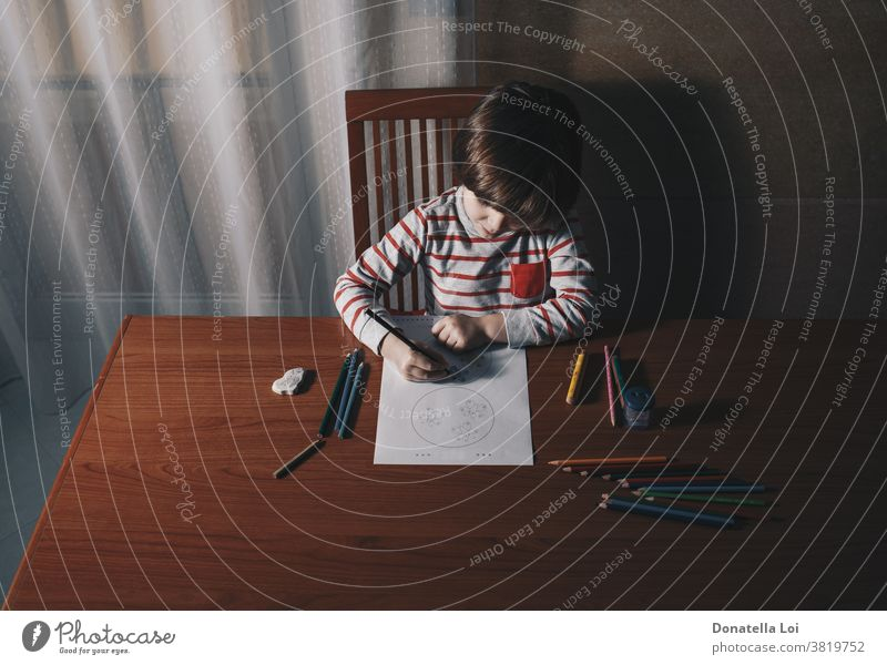 Preschooler drawing on the table in his home alone at home caucasian child childhood children colors concentrate concept conceptual day desk education