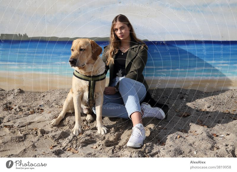Blond girl and a blond Labrador sitting on a wall with graffiti on the beach Landscape Beach Intensive teen kind Nature feminine Uniqueness Exceptional