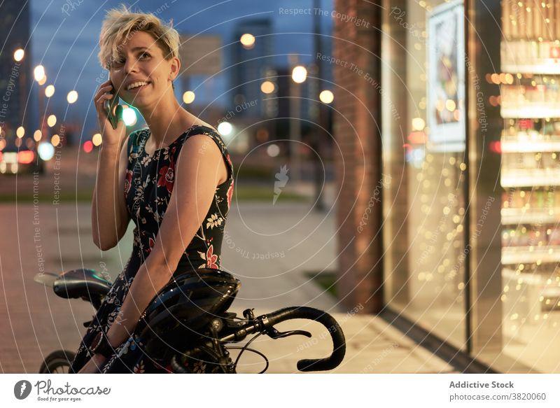 Young woman talking on phone near store and bike Woman dress evening walk girl young riding beautiful city night lights building glass window showcase shop