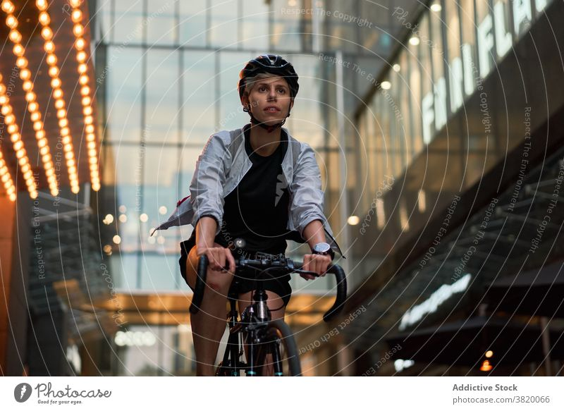 Woman courier cycling near tall building with glass windows in city Cyclist bricked day woman young sports riding summer helmet protective girl delivery