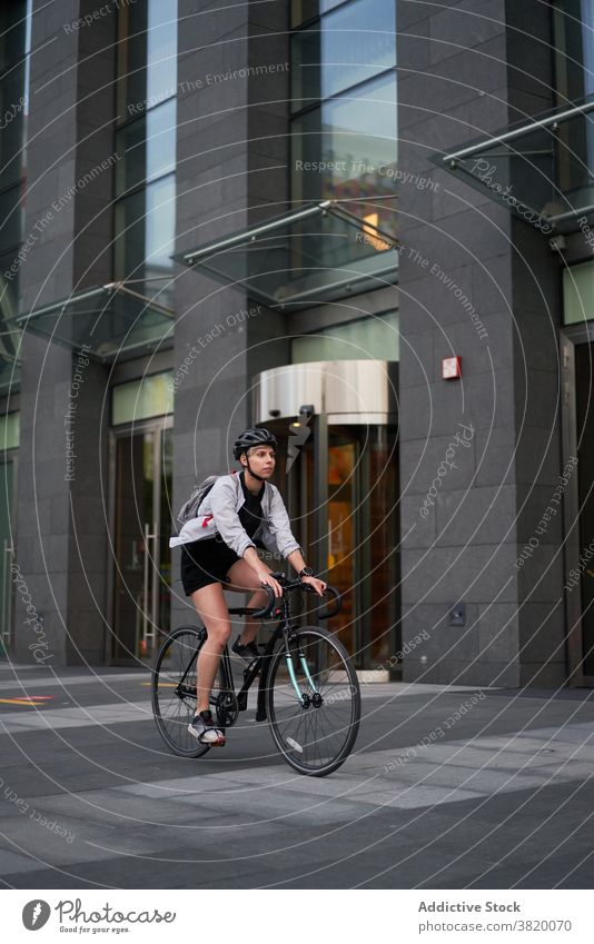 Woman courier cycling near tall building in city Cyclist bricked day woman young sports riding summer helmet protective girl delivery entertainment technology