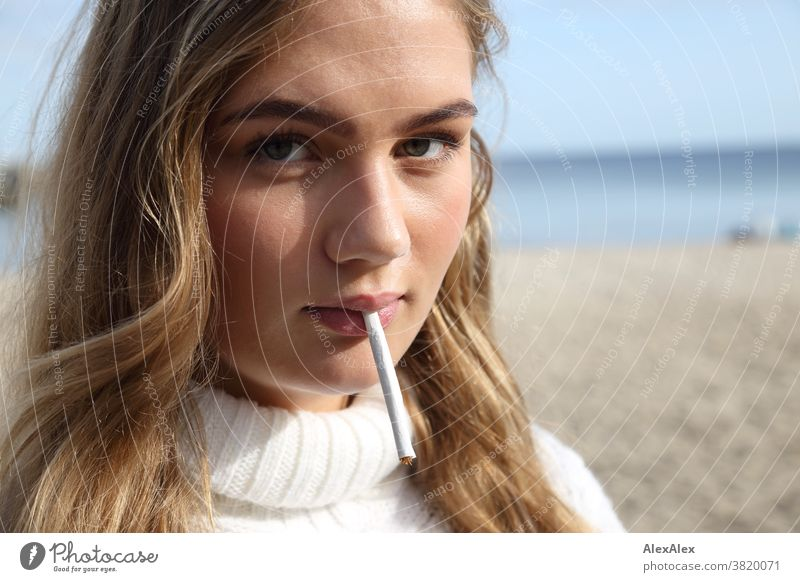 Blonde girl is standing on the east beach and has a self-rolled cigarette in her mouth Landscape Beach Intensive teen kind Nature feminine Uniqueness