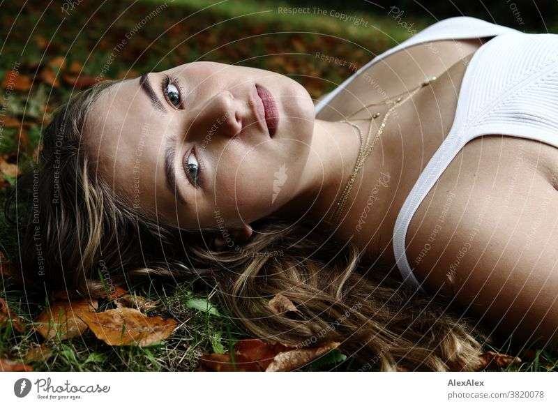 Lateral portrait of a girl in a white strap top lying on an autumn meadow with leaves Landscape Beach Intensive teen kind Nature feminine Uniqueness Exceptional
