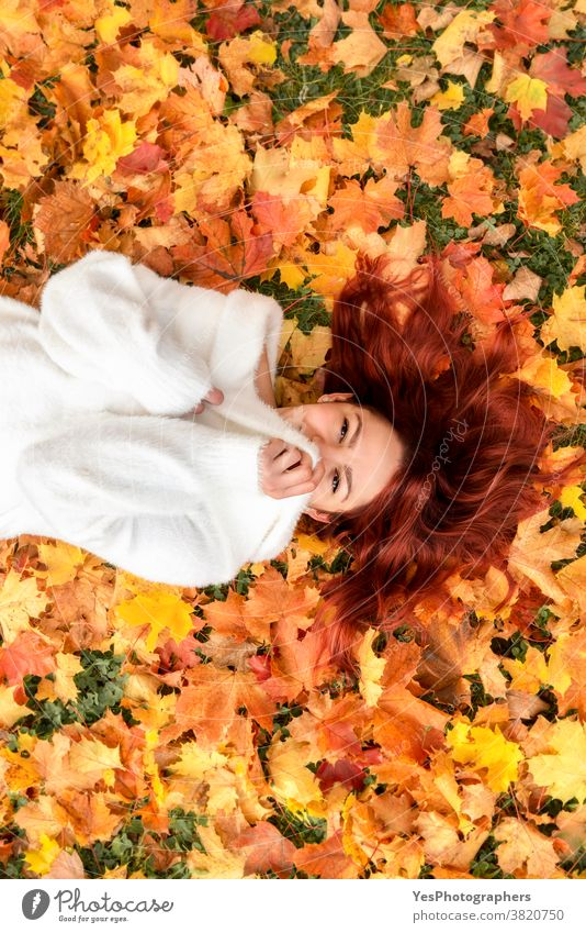 Beautiful redheaded woman lying on autumn leaves. Young woman smiling in autumn scenery 20s November October above view adult alone autumn fashion