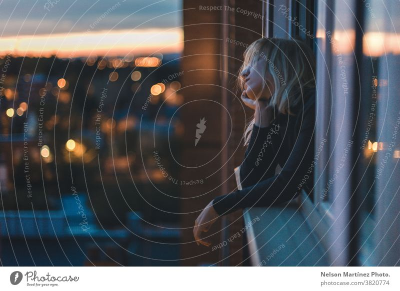 Portrait of a Caucasian woman leaning on the window at blue hour. portrait blonde magic hour Magic Portrait photograph Woman Blonde Colour photo Looking